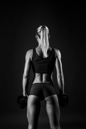 hardworker: You can say she is a hardworker. Shot of sporty female blonde girl showing back off her perfect body on black background