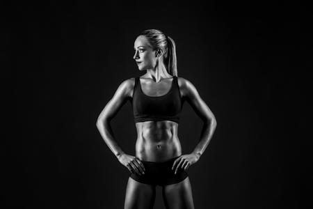 Shot of sporty female blonde girl showing her perfect body on black background