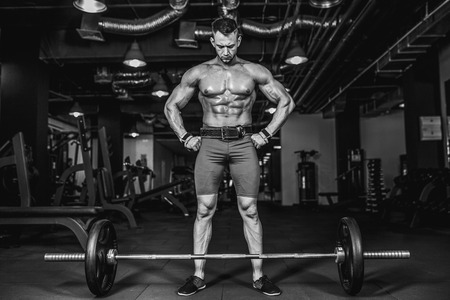 Strong Bodybuilder preparing for deadlift of barbell in the gym,