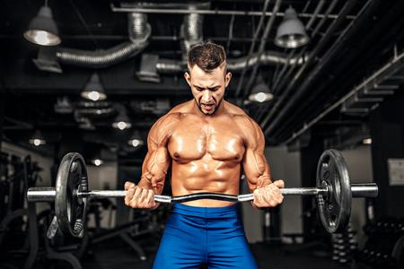 Joven y guapo deportista caucásica culturista que se resuelve con una mancuerna en el gimnasio, que hace el entrenamiento del bíceps.