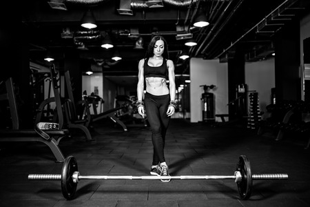Muscular young fitness woman preparing for heavy deadlift exercise in gym Stock Photo