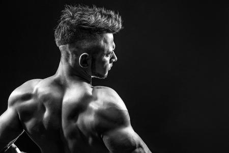 Hombre fuerte de la aptitud atlética que presenta los músculos posteriores, tríceps, latissimus sobre fondo negro Foto de archivo - 75341217
