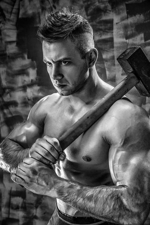 athlete and hammer. guy with a nice toppless muscle fitness body, bodybuilder coach hold big metal hammer Stock Photo