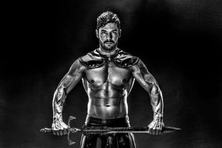 Portrait of handsome muscular gladiator with sword. Studio shot. Black background.