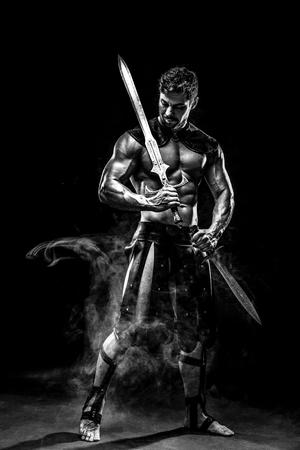 bagging: Portrait of handsome muscular gladiator with sword. Studio shot. Black background.