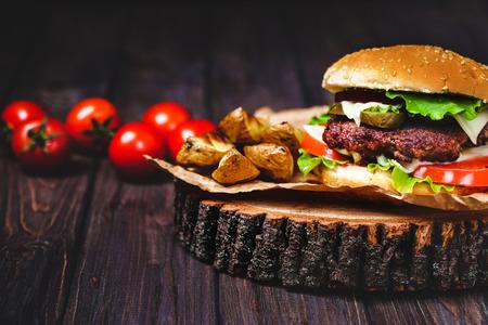 상 추와 마요네즈 집에서 만든 된 쇠고기 햄버거의 근접 촬영 작은 나무 커팅 보드에 재직했습니다. 어두운 배경 스톡 콘텐츠