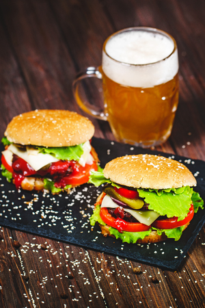 Closeup of mouth-watering, delicious homemade burgers with volatile, onions, ketchup, tomatoes, served with a knife stuck on stone board. Dark wooden background Stok Fotoğraf