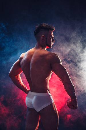 Sterke bodybuilder. Man met perfecte buik, schouders, biceps, triceps en borst, persoonlijke fitness trainer buigt zijn spieren in blauwe, rode rook. Achteraanzicht. Studio shot.