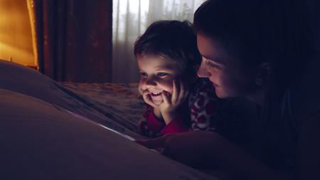 Primer plano de la madre y su pequeña hija mirando tableta. Linda chica mirando el dispositivo, mientras que relajarse en casa. Foto de archivo - 76461629