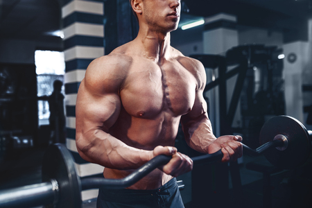 retouched: Muscular bodybuilder guy doing exercises on biceps with big dumbbell in gym
