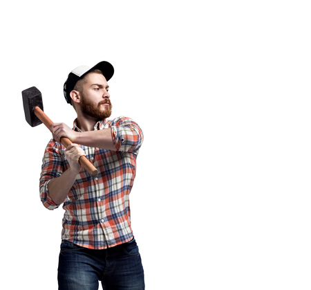 Redhead Bearded man wearing a baseball cap and shirt swunging a hammer with an expression. Stock Photo