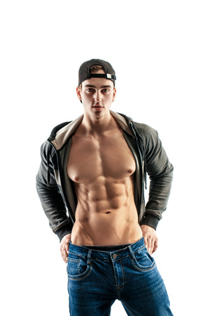 muscular super-high level handsome man in baseball cap posing on white background. showing his six pack press Standard-Bild