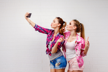 Fashion portrait of two friends posing. modern lifestyle.two stylish sexy hipster girls best friends ready for party.Two young girl friends standing together and having fun. Taking selfie Stock Photo