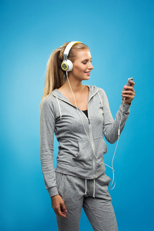 Beautiful blond fit caucasian lady in grey sport  with headphones listening music. Isolated on blue background.