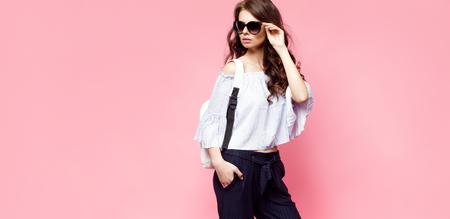 Horizontal studio shot of vogue woman holding hand in pocket and adjusting sunglasses on the pink background.