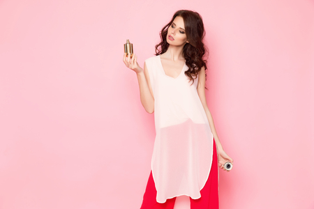 Horizontal studio shot of young attractive woman standing with bottle of toilet water on the pink background. Reklamní fotografie