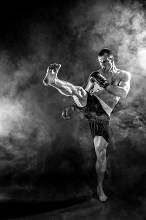 Muscular kickbox or muay thai fighter punching in smoke. Banco de Imagens - 78430829