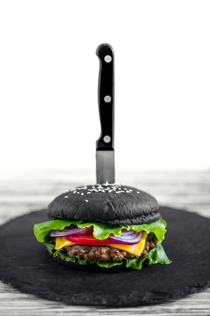 Close up of Homemade Black Burger with Cheese. Cheeseburger with black bun on white wooden background. Junk food. Reklamní fotografie