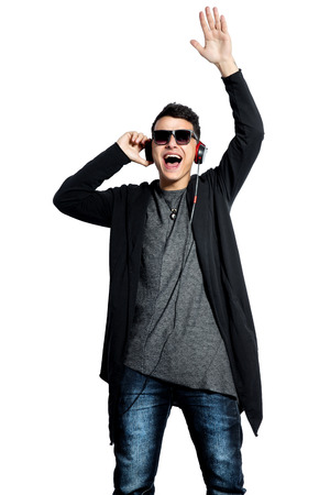Attractive man with headphones raising his hand up while listening the music. Isolate on white