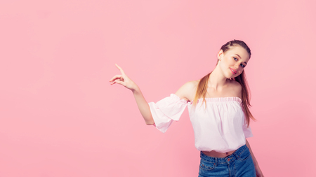 Copy space for advertisement. Colorful portrait of happy smiling young woman pointing away against pink wall. Stock Photo