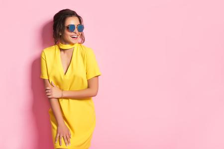 Mooi meisje in kleurrijke kleren die zonnebril dragen die op roze achtergrond in studio stellen. Stockfoto