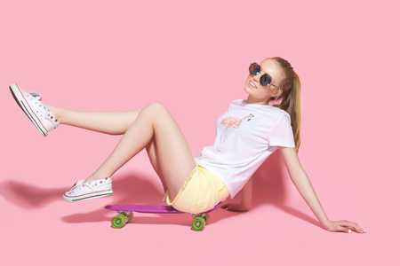 Pretty young casual dressed woman in sunglasses sitting on skateboard. Stock Photo