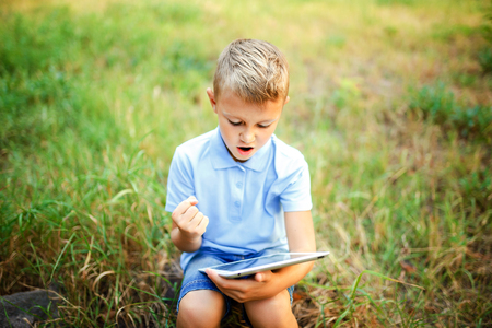 Young kid sittingin the courtyard and playing a game on tablet pc. Stock Photo
