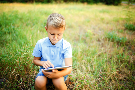 Young kid sittingin the courtyard and playing a game on tablet pc. Reklamní fotografie