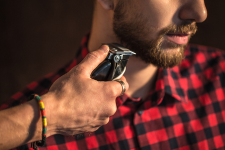 Close-up of Master cuts hair and beard of men in the barbershop, hairdresser makes hairstyle for a young man