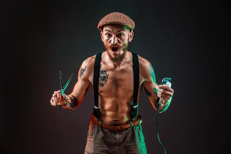 Stylish tattooed shirtless barber gangsta man with razor looking at camera. Standard-Bild