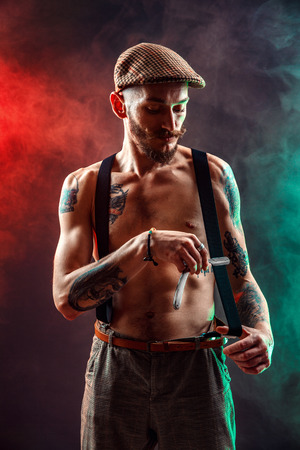 Stylish tattooed shirtless barber gangsta man with razor looking at camera. Foto de archivo