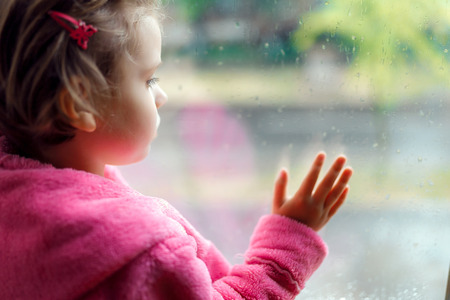 Close up of a Little cute girl in pink bathrobe stares sadly out of a window. Sitting on the window sill. The child looks out of the window.