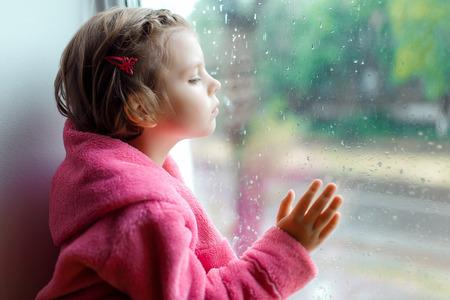 残念ながら窓の外のピンクのバスローブの視線で、かわいい女の子のクローズ アップ。窓枠の上に座っています。子供は、窓から見えます。 写真素材 - 80784388