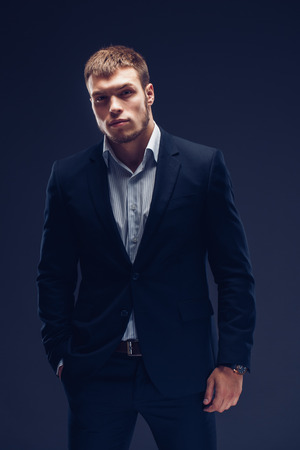 Fashion young man black suit on dark background