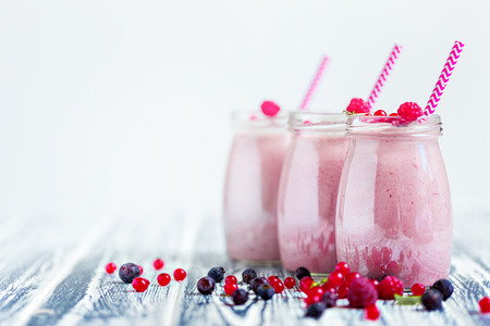 Several glass transparent jars with purple yogurt in them mixed with berries.
