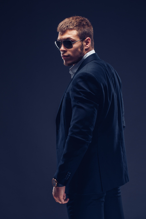 Fashion young man in sunglasses, luxury suit on dark background. Back view Stock Photo