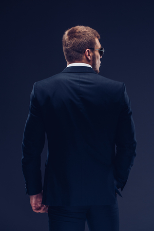 Back view Fashion young man in suit on dark background