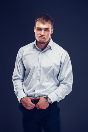 Fashion young man holding hands on Belt of pants and grimaces his face while looking at the camera Stock Photo