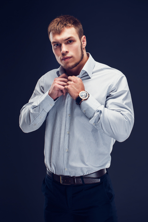Fashion young beautiful, sexy, sporty guy in a white striped classic shirt button up his collar on dark background