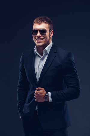 Fashion young smiling man in sunglasses, luxury suit on dark background