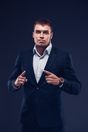 Fashion young man in suit on dark background showing with his fingers.