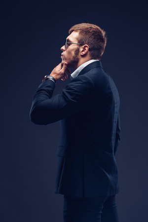 Side view of fashion young man in sunglasses, luxury suit on dark background. Touches his chin and looking away Stock Photo
