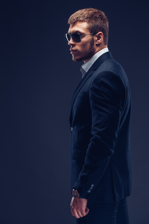Side view of fashion young man in suit on dark background Stock Photo