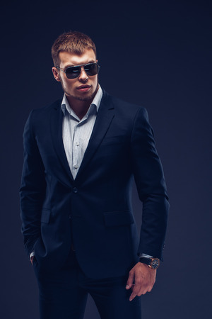 Fashion young man in sunglasses, luxury suit on dark background. Looking away Stock Photo