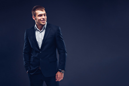 Fashion young smiling man in suit on dark background. Looking away.