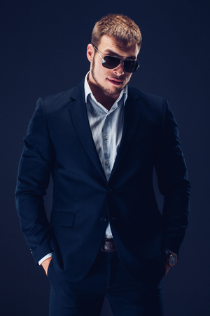 Fashion young man in sunglasses, luxury suit on dark background Stock Photo