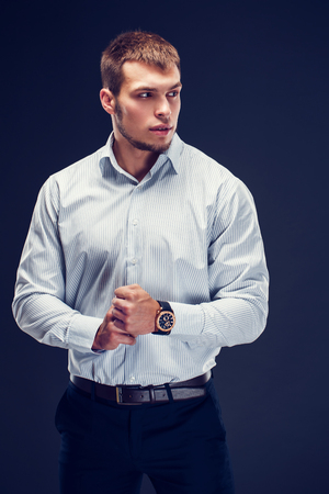 Fashion young man holding hand with watch on dark background. Looking away