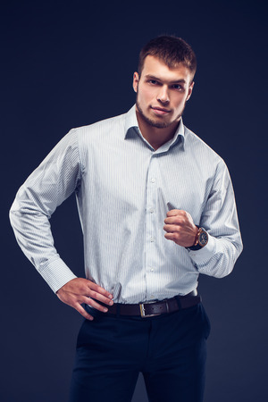 Fashion young serious man in stripped shirt clenches ones hand into a fist and looking at camera on dark background