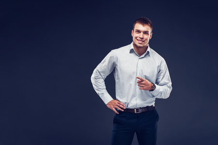 Fashion young serious man in stripped shirt points finger, smiling and looking at camera on dark background. Copyspace