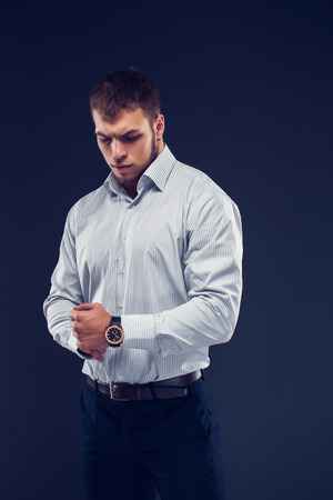 Fashion young man holding hand with watch on dark background